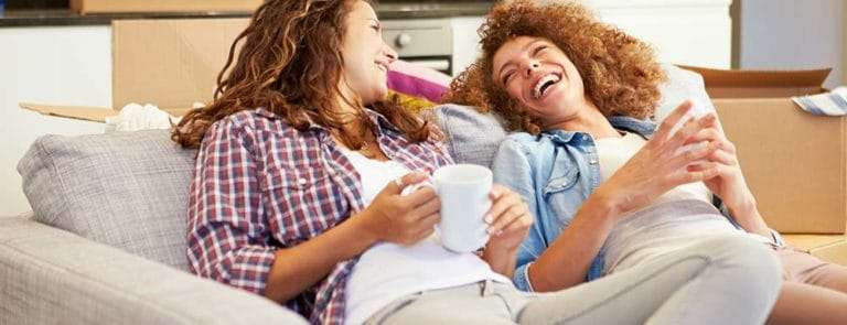 Two female friends sitting on a sofa drinking tea and laughing