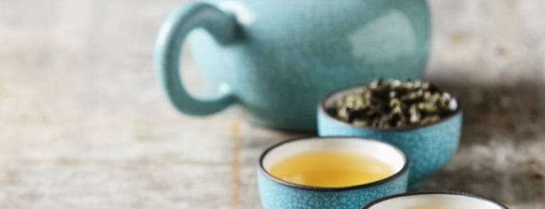 Blue teapot and cups filled with tea