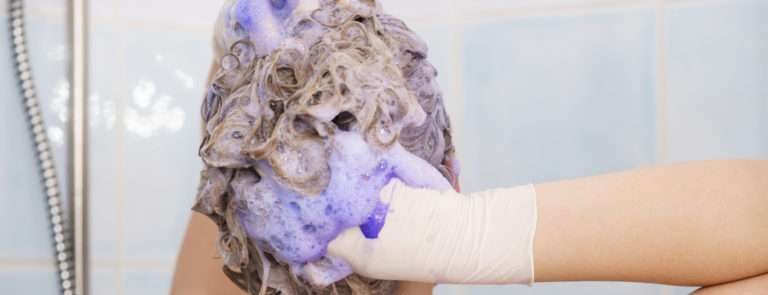 A lady wearing gloves and massaging purple shampoo into her hair.