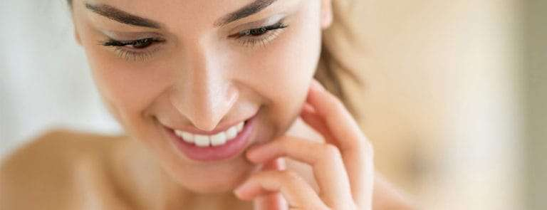 Woman smiling with hand on face