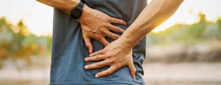 man with back pain holding back