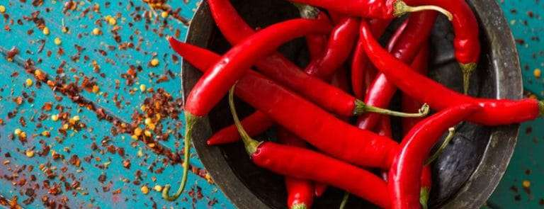 A bowl of red chilies with chili seeds