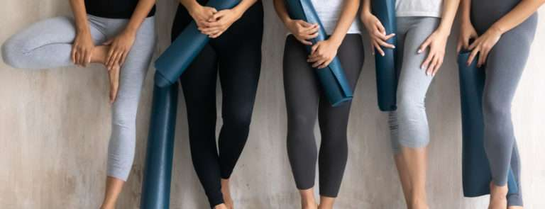 group of women with excersize mats going to yoga vs pilates