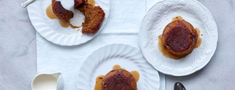 Three sticky toffee puddings made with dates, served with toffee sauce and pouring cream