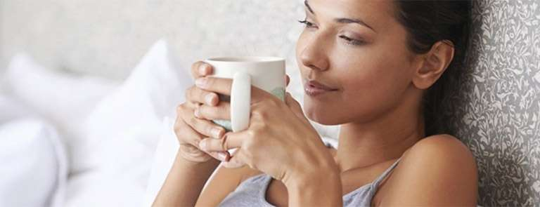 A Woman in Bed holding a Mug