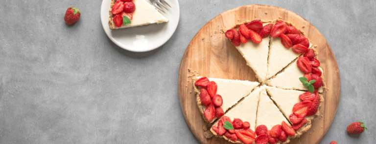 A vegan cheesecake, topped with strawberries.