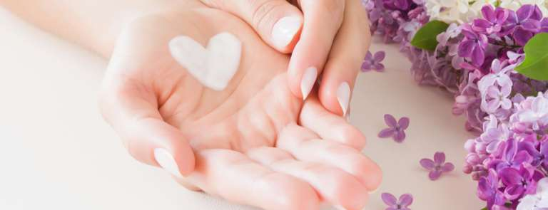 closeup of womans hands with heart shaped cream patch