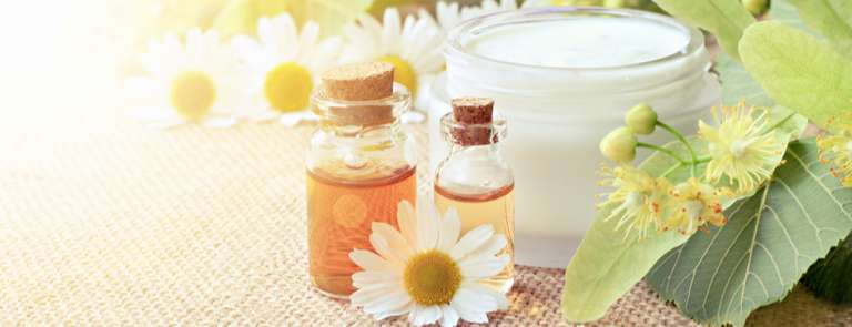 chamomile flowers with cosmetic bottle essential oil