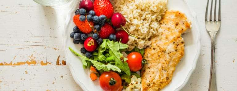 A plate with fish, rice, a salad and fruit on it