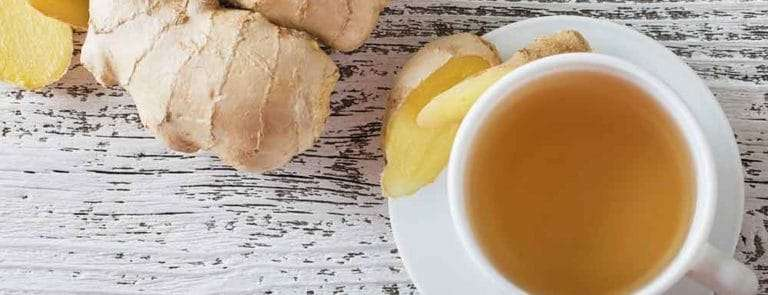 Ginger and teacup on a wooden surface