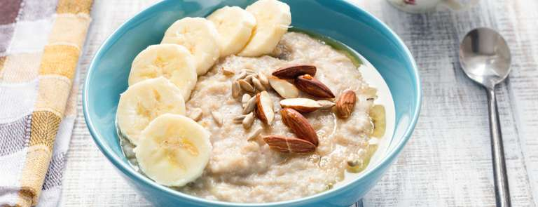 bowl of porridge with banana and almonds and honey