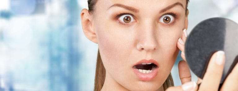 woman shocked at acne on skin