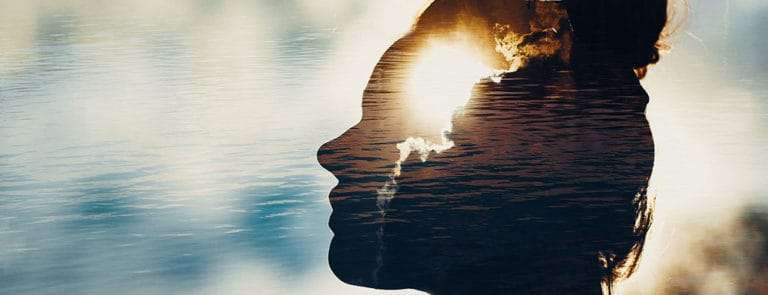 Transparent silhouette of woman's head in front of a river