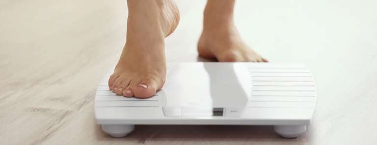 woman stepping onto weight scale