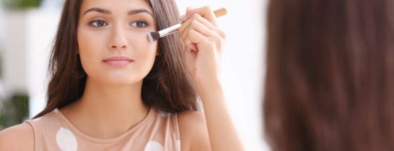 a woman applying foundation on her dry skin