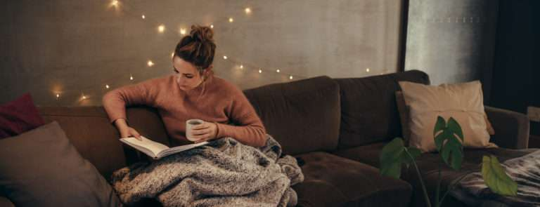 woman with a cosy blanket snuggled on her sofa reading a book with a hot drink