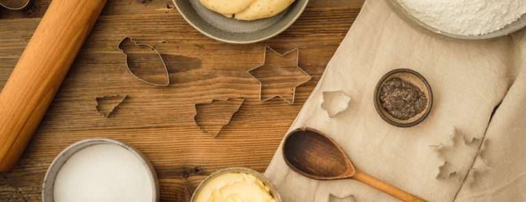 A baking set up with a wooden spoon, rolling in and almond butter in a bowl.