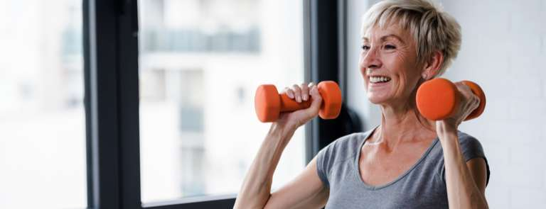 mature menopausal woman holding weights for strength training