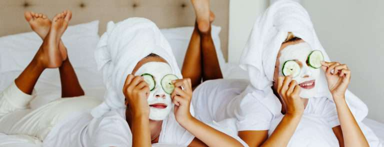 Two ladies in face masks, with cucmbers on their eyes, lying on a bed whilst wearing wrapped towels around their heads.