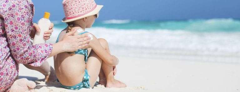A parent applying sun cream to her child's back