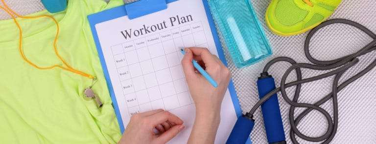 Someone writing in their workout plan with exercise equipment page
