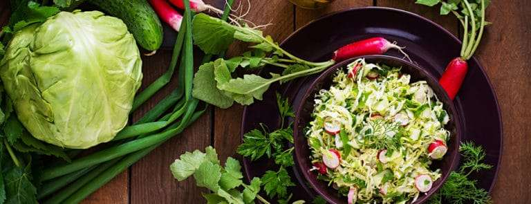 Vitamin salad of young vegetables: cabbage, radish, cucumber and fresh herbs.