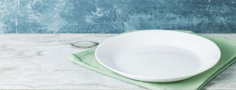 empty dinner plate on cloth and table