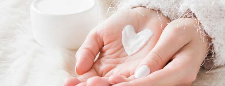 woman's hands with cream in the shape of a heart