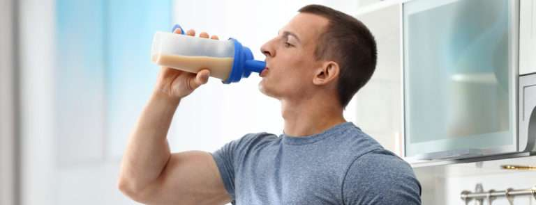 An athletic young man drinking a protein shake in the kitchen.