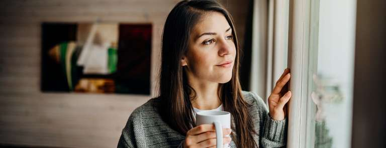 woman with cup of tea looking out window