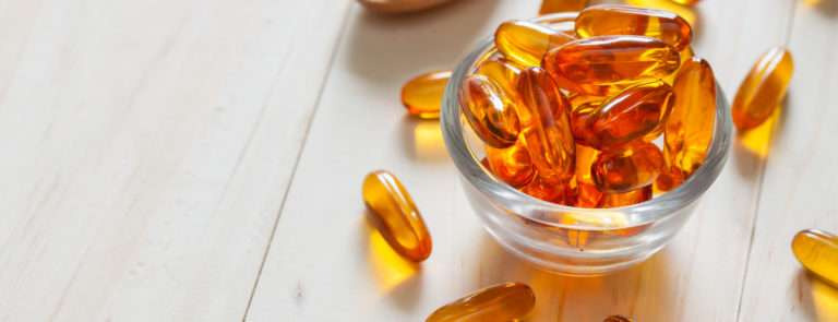 A table filled with omega 3 capsules in a bowl, on a spoon and scattered around.