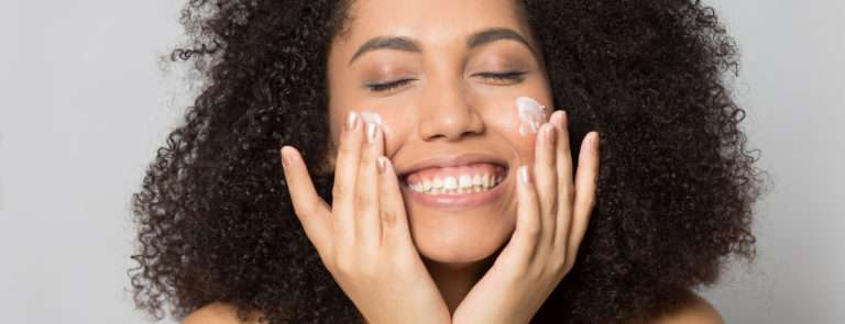 a woman with clear skin applying face cream