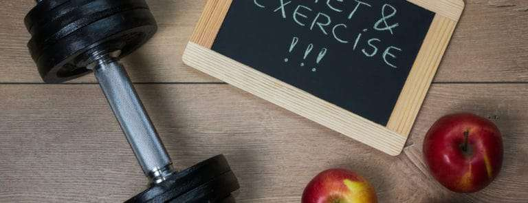 A weight, some apples, and a chalkboard with diet & exercise written on it