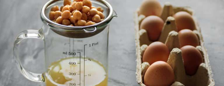 A sieve with chickpeas, draining into a jar and a carton of eggs next to it.
