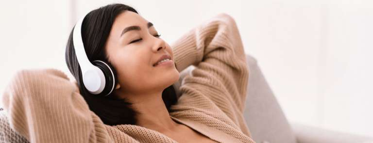 asian woman listening to podcast on headphones and relaxing