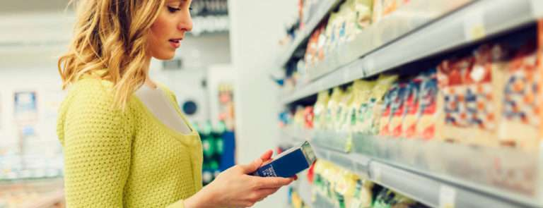 Woman in a shopping aisle looking at the ingredients of a product from a shelf
