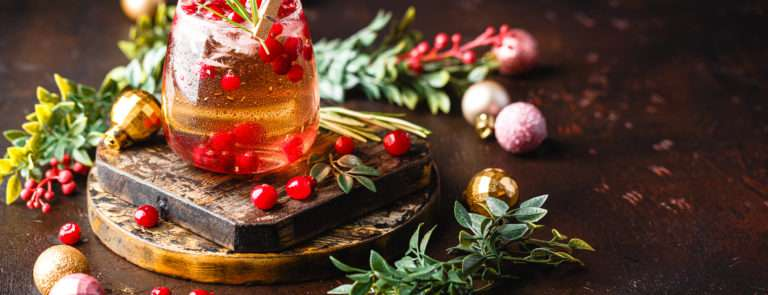 A festive drink with cranberries inside, on a wooden board, surrounded by cranberries, baubles and pine.