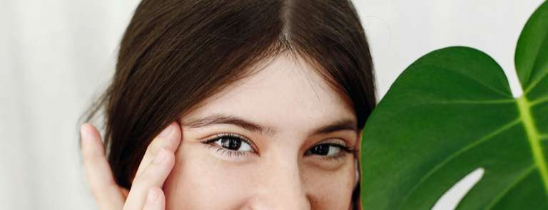 woman holding skin by eyes ready for under eye beauty treatment