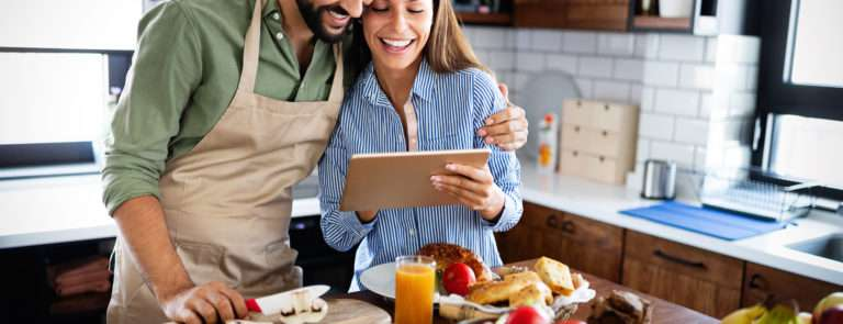 A couple looking at an electronic tablet, whilst cooking lunch.