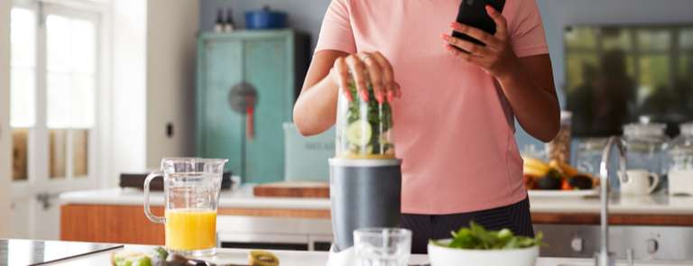 woman blending smoothie and counting calories on phone
