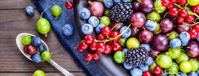 mixed berries in a bowl over flowing onto a blue cloth placed on a wooden table, with a spoon of berries by the side