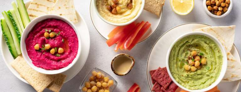 Hummus and dip selection with carrots and chickpeas in a bowl.