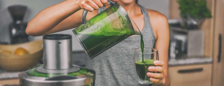 woman in kitchen pouring homemade green juice for juice diet