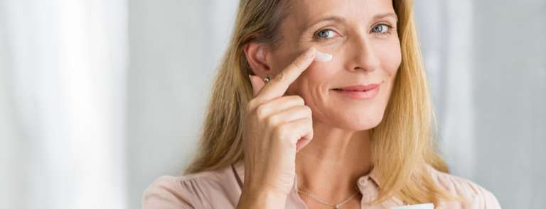 woman applying collagen cream to face