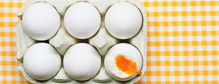 half a dozen eggs with one cracked and the yolk showing