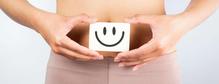 woman showing card of smiley face next to stomach