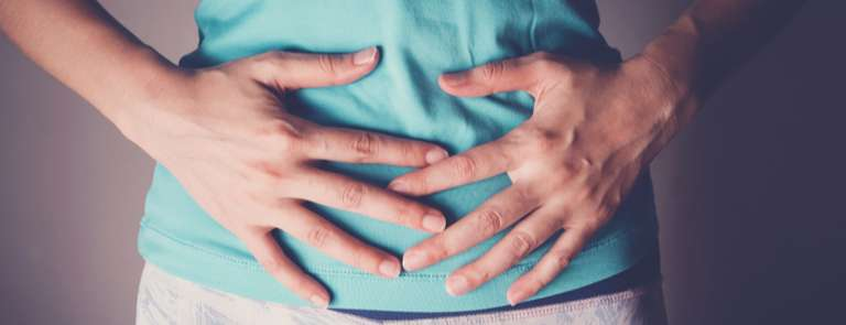 woman with hands on stomach digestive health