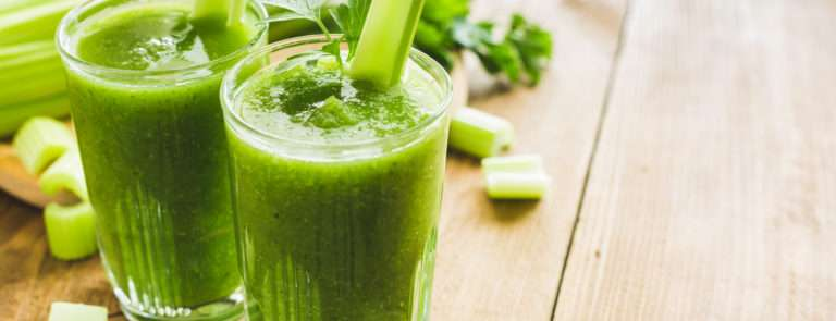 2 celery juices with celery sticks on top and chopped celery around.
