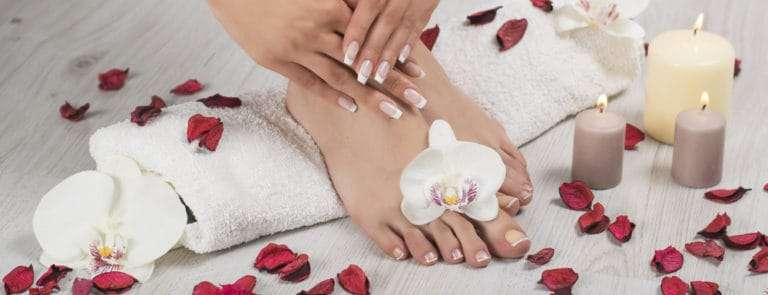 female feet and hands with french manicure