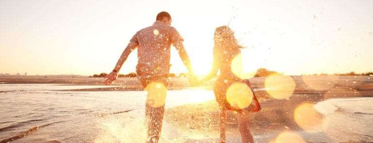 couple splashing in the waves at sunset on a beach